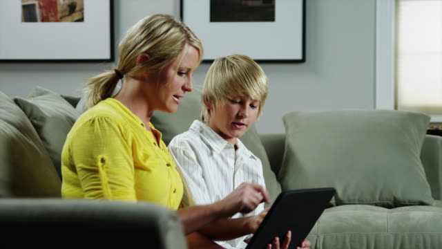 ms ds mother and son (10-11) using digital tablet on sofa / orem, utah, usa - orem utah stock videos & royalty-free footage
