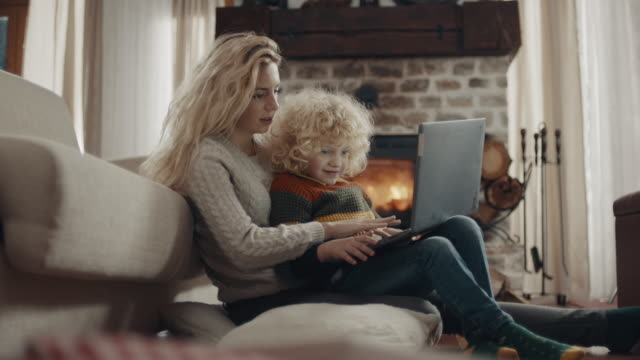 mother and son using laptop together - one parent stock videos & royalty-free footage