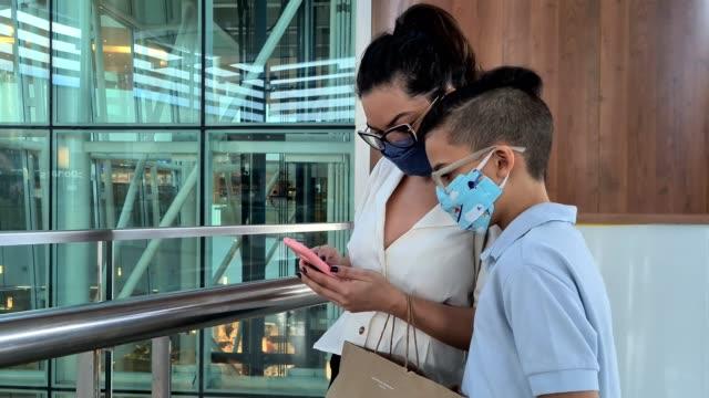 stockvideo's en b-roll-footage met moeder en zoon die slimme telefoon in het winkelende centrum tijdens pandemie gebruiken - rondrijden