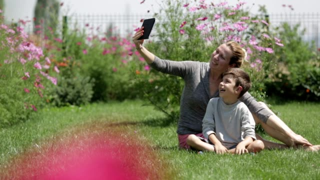 Mother and son using tablets in front or backyard