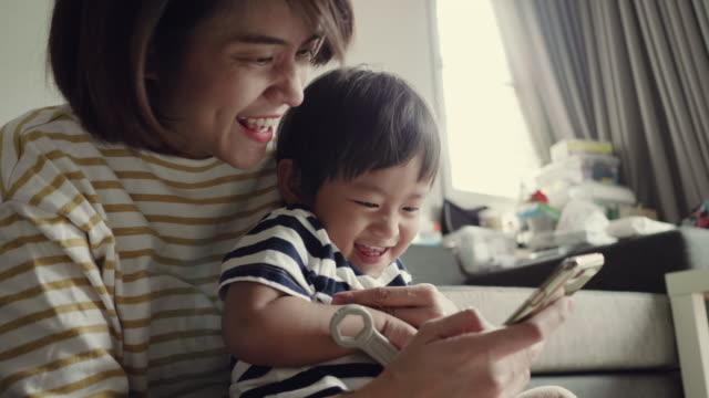 母と息子のビデオを携帯電話でチャット - 家の中点の映像素材/bロール