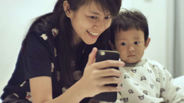 mother and son video chatting on mobile phone - 6 11 months stock videos & royalty-free footage