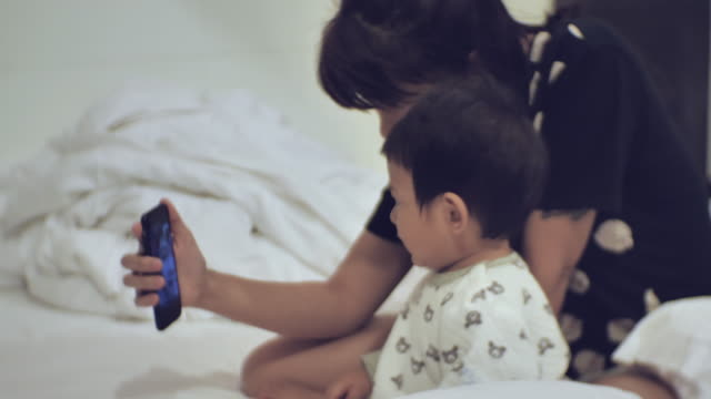 mother and son video chatting on mobile phone - video conference stock videos & royalty-free footage