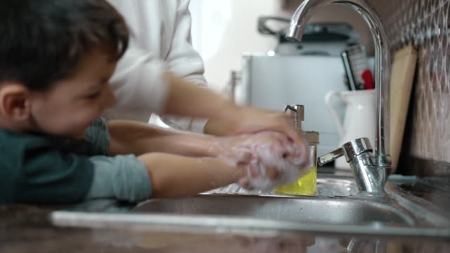 mother and son wahing hands together in kitchen - soap sud stock videos & royalty-free footage