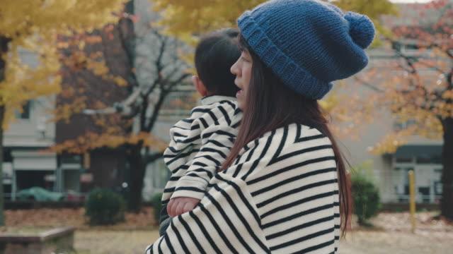 vidéos et rushes de mère et fils à pied dans le parc au japon. - son