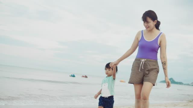 母と息子は裸足で歩き、白い砂の海岸で手をつないで - 裸足点の映像素材/bロール