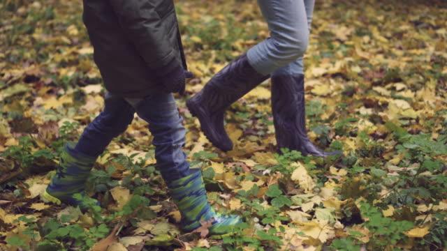 stockvideo's en b-roll-footage met moeder en zoon wandelen in rubber laarzen in herfst bos - rubber
