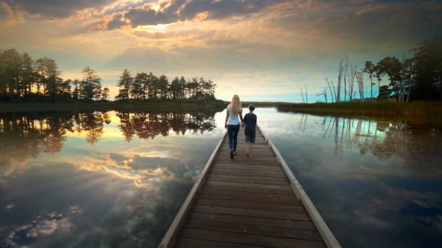 mother and son walking on dock of lake with beautiful sunset, oregon - back lit stock videos & royalty-free footage