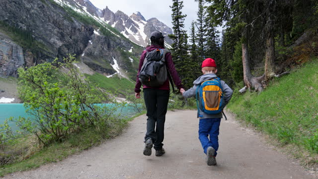 mother and son walking on lake louise lakeshore trail in the morning, alberta, canada - tourism stock videos & royalty-free footage