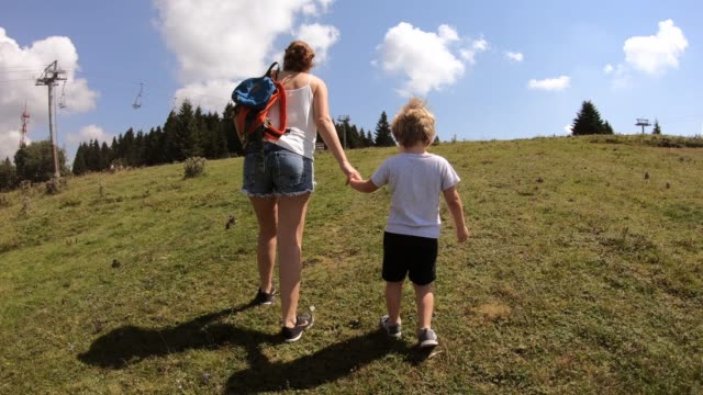 mother and son walking on mountain - rucksack stock videos & royalty-free footage