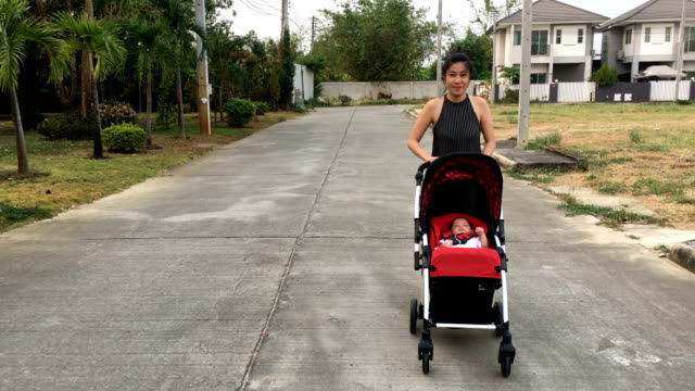 mother and son walking relaxation with a little boy sitting on baby stroller