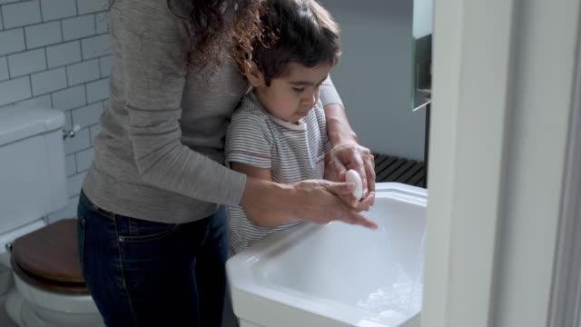 vídeos y material grabado en eventos de stock de mother and son washing hands - familia con un hijo