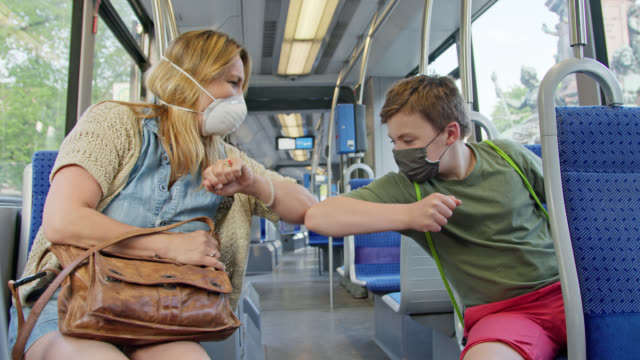 mother and son wearing protective mask against contagious virus infection in tramway trambahn greeting with elbows. - 肘点の映像素材/bロール