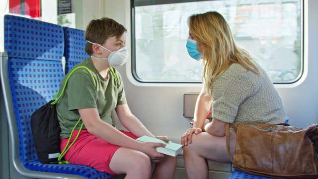 mother and son wearing protective masks to prevent virus infection sitting in suburban train and discussing. - passenger train stock videos & royalty-free footage