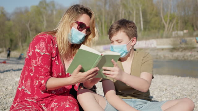 mother and son with face masks to protect and prevent from the infection with coronavirus reading a book outside. - two generation family stock videos & royalty-free footage