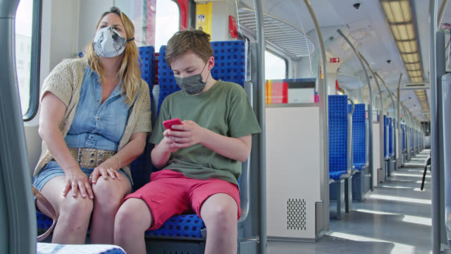 mother and son with stylish diy protective masks sitting in suburban train waiting to arrive at destination. - passenger train bildbanksvideor och videomaterial från bakom kulisserna