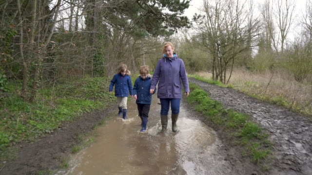 mother and sons walking through a muddy park - mud stock videos & royalty-free footage