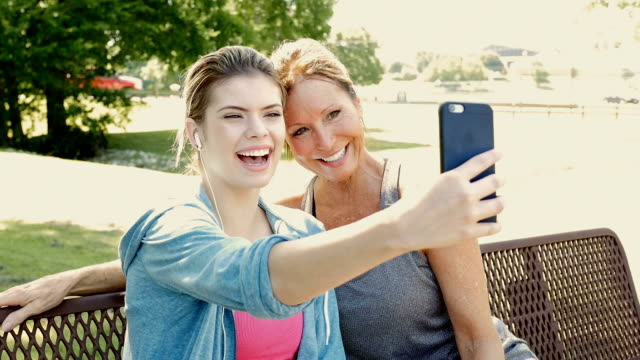 Mother and teen daughter taking a selfie photo together outdoors at park