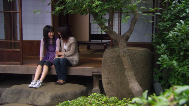 WS Mother and teen girl sitting side by side at entrance to house/ Tokyo, Japan