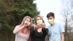 Mother and Teenage Children in Face Masks Taking Selfies