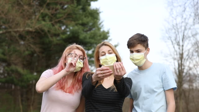 mother and teenage children in face masks taking selfies - 18 19 years stock videos & royalty-free footage