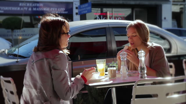 MS Mother and teenage daughter eating breakfast at café on high street armadale / Melbourne, Victoria, Australia