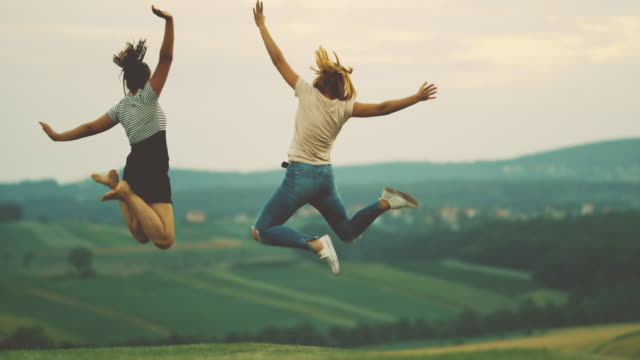 MS Mother and teenage daughter jumping for joy in rural field