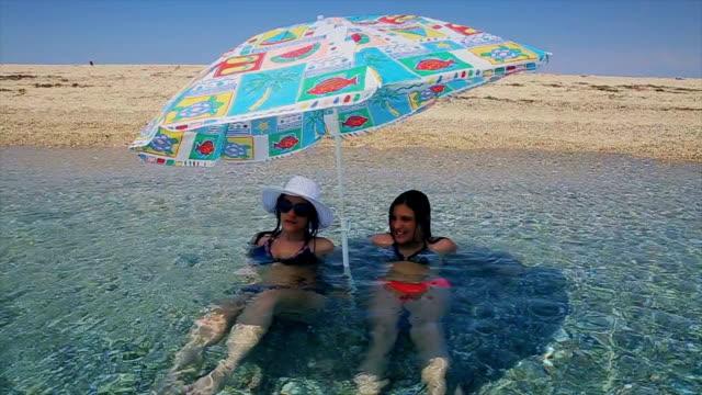 mutter und tochter im teenageralter im wasser unter einem sonnenschirm sonnenschirm in einem see sitzen frei fühlen - bikini stock-videos und b-roll-filmmaterial