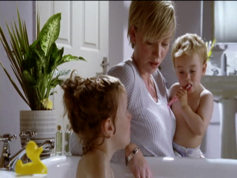 mother and toddler next to a young brother and sister sharing a bath, who are playing with rubber ducks and splashing each other with water - naked stock videos & royalty-free footage