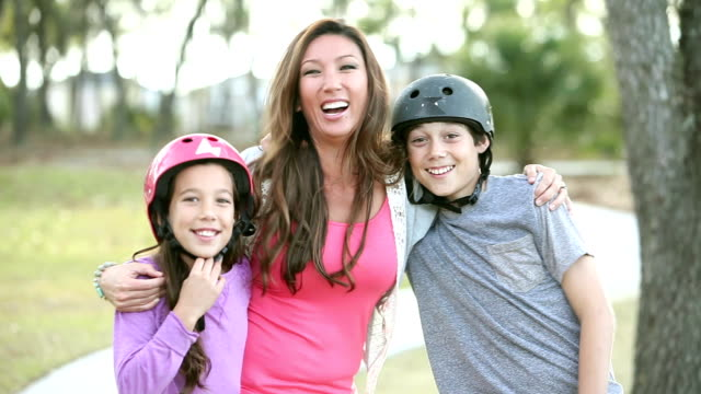 Mother and two children skateboarding in park toward camera