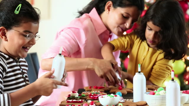 ms mother and two daughters decorating gingerbread cookies for christmas / richmond, virginia, united states - keks stock-videos und b-roll-filmmaterial