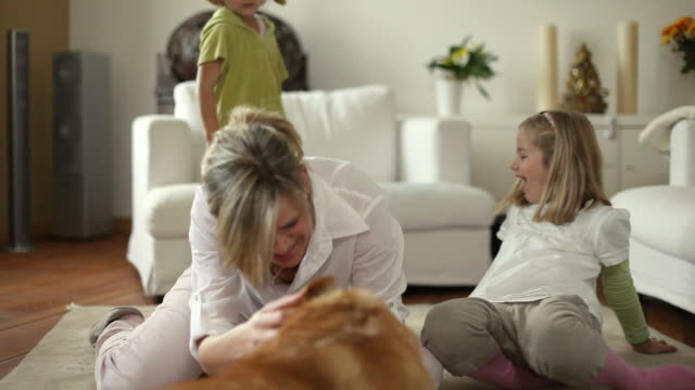 MS DS Mother and two daughters (4-6) playing with dog in living room / Potsdam, Brandenburg, Germany