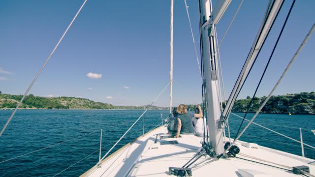ds-mutter und zwei töchter, die entspannend auf einem deck eines segelbootes - küste stock-videos und b-roll-filmmaterial