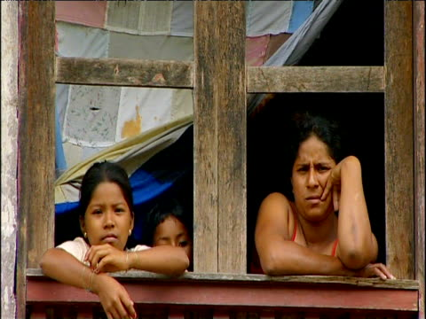 mother and two daughters stare out of window of primitive hut ecuador - two generation family stock videos & royalty-free footage
