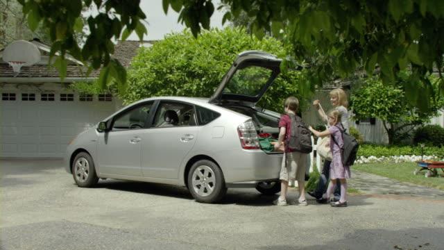 vídeos y material grabado en eventos de stock de ms pan mother and two kids (9-11) loading bags into trunk and getting in car parked in driveway, encino, california, usa - coche híbrido