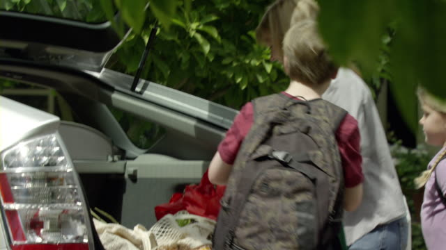 ms shaky. pan mother and two kids (9-11) unloading groceries from trunk, encino, california, usa - 積荷を降ろす点の映像素材/bロール