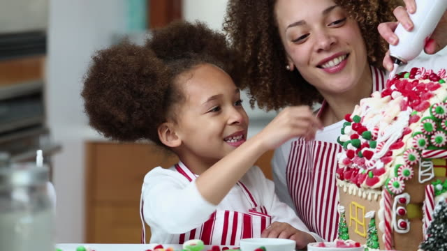 MS PAN Mother and Young Daughter Decorating Gingerbread House for Christmas / Richmond, Virginia, United States