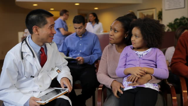 MS Mother and young daughter meet with doctor in hospital waiting room / Albany, New York, United States
