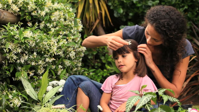 mother and young daughter putting flowers in their hair / cape town, western cape, south africa - ambientazione video stock e b–roll
