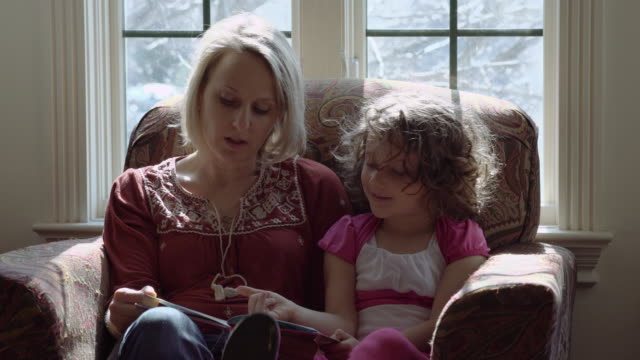 mother and young daughter reading together - asking stock videos & royalty-free footage