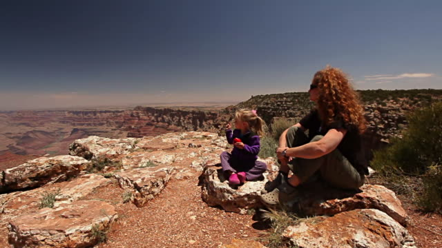 Mother and young daughter rest on the rim of the Grand Canyon while little girl eats apple