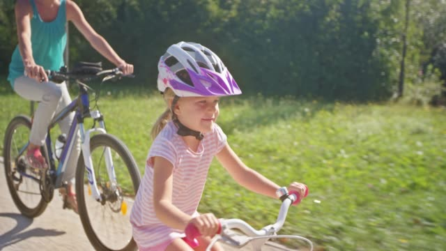 ts mother and young daughter riding bikes in the sunny park - sports helmet stock videos & royalty-free footage