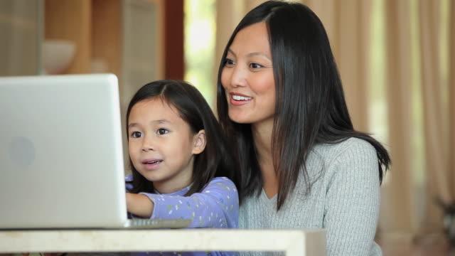 vídeos de stock, filmes e b-roll de ms pan mother and young daughter (6-7) using laptop computer / richmond, virginia, usa - usa