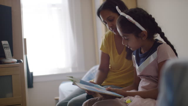 Mother and young girl sitting on bed reading book together