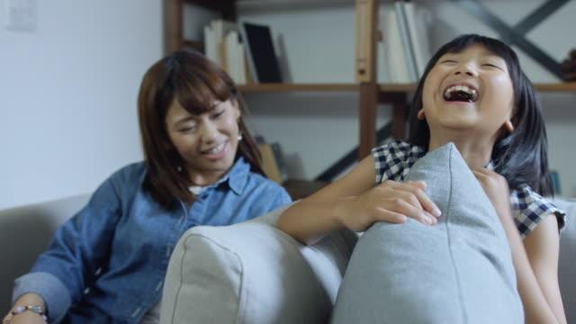母親と少女はソファの上に座って、笑って - 30代点の映像素材/bロール