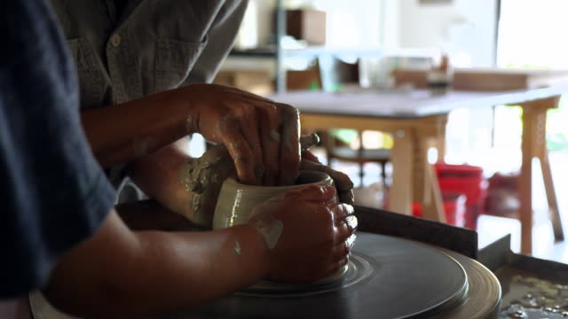 cu mother and young son making mug together at potters wheel in garage studio - a helping hand stock videos & royalty-free footage