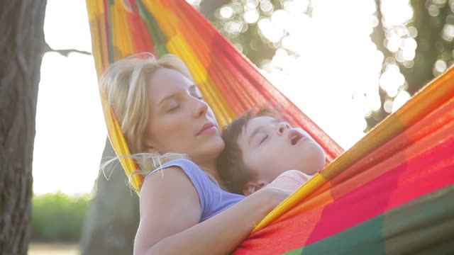 mother and young son napping together in hammock - napping stock-videos und b-roll-filmmaterial