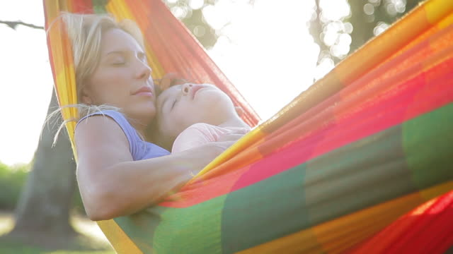 vídeos de stock e filmes b-roll de mother and young son napping together in hammock - dormitar