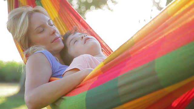 vidéos et rushes de mother and young son napping together in hammock - hamac