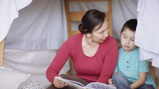 mother and young son reading a book in a sheet fort - native american ethnicity stock videos & royalty-free footage